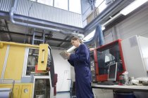 Female engineer monitoring factory machinery using digital tablet — Stock Photo