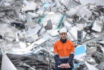 Porträt eines Arbeiters, der in einer Aluminium-Recyclinganlage vor Schrott steht — Stockfoto