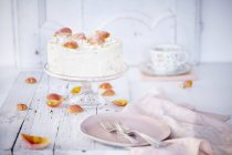 Still life of cream cake on cake stand garnished with rose petals — Stock Photo