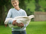 Portrait of Boy Holding Goose outdoors — Stock Photo