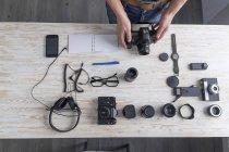 Overhead view of male photographer preparing camera on studio desk — Stock Photo