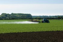 Tractor and crop sprayer spraying in countryside field — Stock Photo
