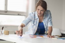 Young female artist drawing by table indoors — Stock Photo