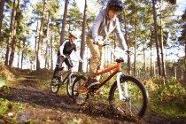 Братья-близнецы гоняют на велосипедах BMX через грязный лес — стоковое фото