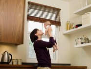 Mother holding her baby up in the air — Stock Photo