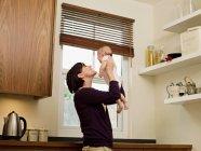 Madre sosteniendo a su bebé en el aire - foto de stock
