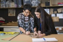 Zwei Näherinnen mit gebogenem Lineal auf Schneidermuster in der Werkstatt — Stockfoto