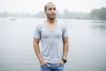 Portrait of young man by lake — Stock Photo