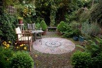 Flores en jarrones con sillas y un jardín inglés - foto de stock
