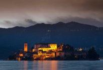 Edifícios da aldeia na ilha iluminada à noite — Fotografia de Stock