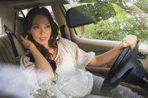 Jeune femme avec la main dans les cheveux en voiture — Photo de stock