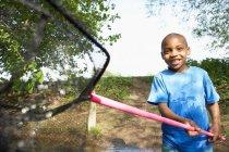 Boy playing with fishing net — Stock Photo