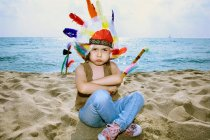 Toddler in Indian headdress on beach — Stock Photo