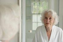 Ältere Frau bewundert sich im Spiegel — Stockfoto