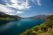 Still lake with mountains under blue cloudy sky — Stock Photo