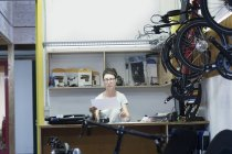 Woman in bicycle workshop behind counter looking at paperwork — Stock Photo