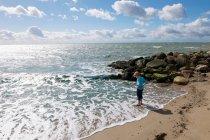 Junge steht in der Brandung am Strand — Stockfoto