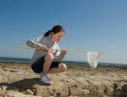 Ragazza che gioca con la rete da pesca sulla spiaggia — Foto stock