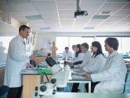 Professeur de sciences en classe de biologie avec des étudiants en laboratoire scolaire — Photo de stock