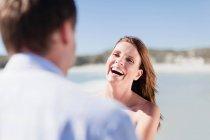 Sorridente coppia a piedi sulla spiaggia — Foto stock
