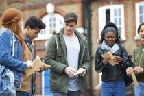 Junge Erwachsene Studenten öffnen Prüfungsergebnisse auf dem campus — Stockfoto