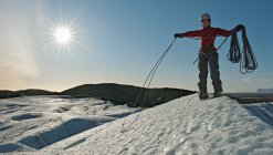 Climber coiling rope on glacier — Stock Photo