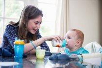 Chica alimentación bebé hermano en la mesa - foto de stock