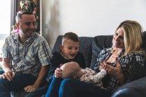 Famiglia seduta sul divano, bambino sulle ginocchia della madre — Foto stock