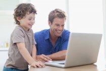 Pai e filho usando laptop juntos — Fotografia de Stock