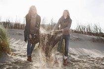 Femmes agitant couverture de plage — Photo de stock