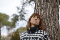 Женщина, прислонившись Дерево носящий в наушники, глаза закрыты — стоковое фото