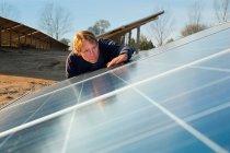Operaio esaminando pannelli solari, messa a fuoco selettiva — Foto stock