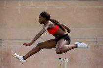 Runner jumping over hurdles on track — Stockfoto