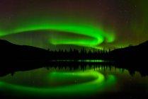 Aurora Boreal que reflejan en el agua del lago en la noche - foto de stock