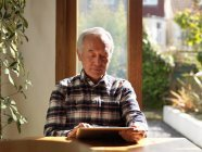 Older man using tablet computer at table — Stock Photo