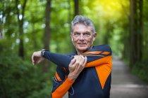 Старші чоловіки бігун розтягування зброї в лісопарку — стокове фото