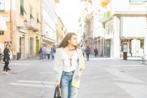 Женщина, стоящая на улице и глядящая в сторону — стоковое фото
