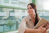 Молодая женщина держит в цифровом планшете в офисе — стоковое фото