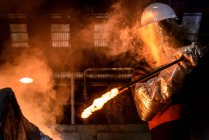 Worker stiring molten metal in foundry furnace — Stock Photo