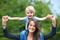 Мать носит сына на плечах, сосредоточься на переднем плане — стоковое фото