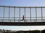 Бегун, пересекающий мост днем — стоковое фото