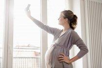 Donna incinta che cattura maschera di se stessa — Foto stock