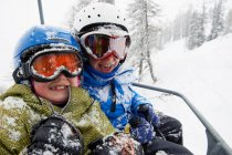 Snow covered children in ski lift, focus on foreground — Stock Photo