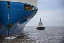 Обрезанное изображение буксира рядом с большим кораблем в море — стоковое фото