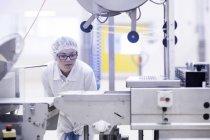 Trabajador de fábrica que opera maquinaria de producción de alimentos - foto de stock