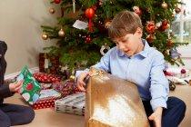 Дітей, відкриття різдвяні подарунки — стокове фото