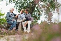 Senior man and mid adult couple sitting on log — Stock Photo
