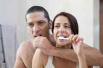 Couple brushing their teeth in bathroom — Stock Photo