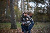 Ragazzo dando amico a cavalluccio nella foresta — Foto stock