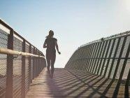 Женщина, бегущая по Скайбриджу, избирательный фокус — стоковое фото